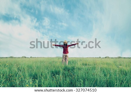 Young woman in straw hat standing with raised arms on meadow in summer. Concept of happiness and carefree