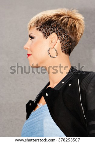 Young woman in style of urban fashion. Short blonde leopard skin hairstyle. Dressed with motorcycle black jacket and a blue dress. Urban fashion photography. Vertical image.