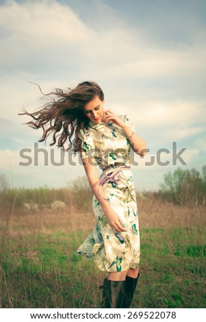 young woman in summer dress in grass field, hair in motion from wind, retro look and colors - stock photo