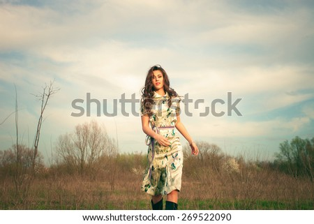 young woman in summer  dress run across  field,   retro look and colors - stock photo