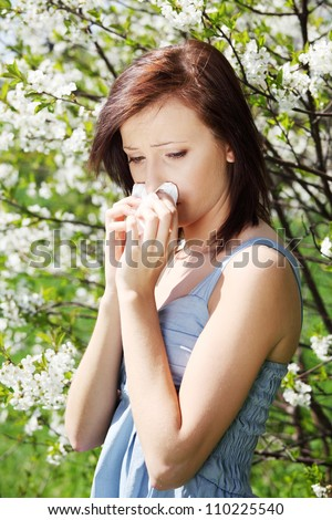 Young woman in summer dress standing among blossom trees during sunny day  and wiping her nose. Girl with runny nose, having allergy and holding a tissue next to her face.