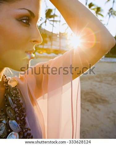 Young woman in summer dress standing on the beach - stock photo