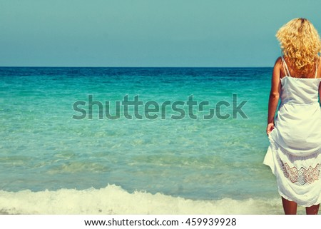 Young woman in summer white dress standing on beach and looking to the sea.