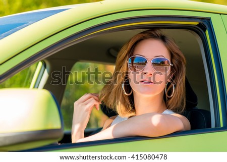 young woman in sunglasses behind the wheel - stock photo