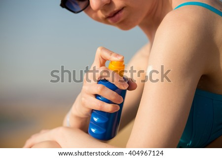 Young woman in sunglasses holding bottle of sunscreen lotion, spraying sunblock cream on shoulder before tanning, close up - stock photo