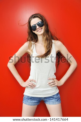 Young woman in sunglasses on red background - stock photo