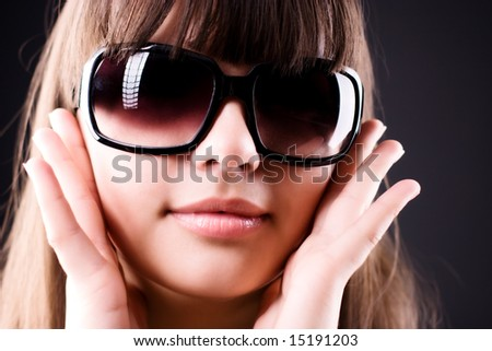 Young woman in sunglasses portrait. On dark background. - stock photo