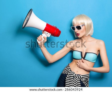 young woman in sunglasses with a megaphone in his hand on a turquoise background - stock photo