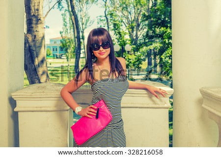 Young woman in sunglasses with pink handbag, copyspace - stock photo