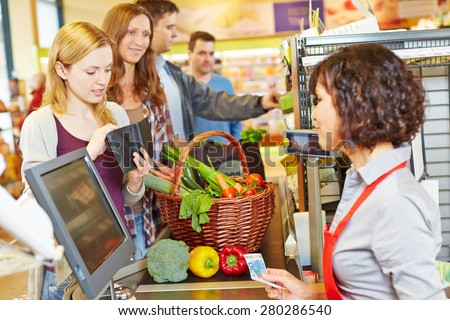 Young woman in supermarket queue is missing money for payment - stock photo