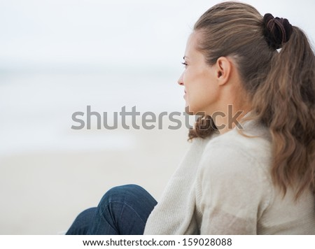 Young woman in sweater sitting on lonely beach and looking into distance