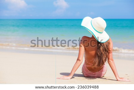 young woman in swimsuit and sunglasses lying on beach - stock photo