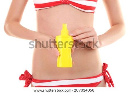 Young woman in swimsuit holding spray tanning isolated on white - stock photo