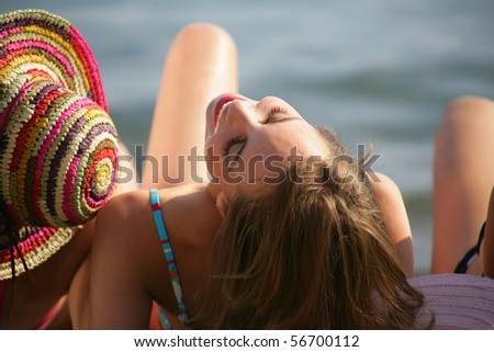 Young woman in swimsuit laid on the sand - stock photo