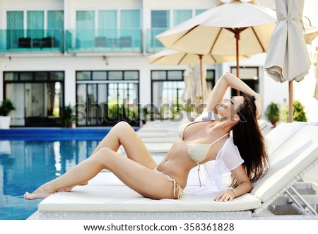 Young woman in swimsuit laying on chaise-longue  - stock photo