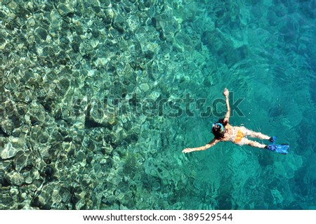 Young woman in swimsuit snorkeling in clear shallow tropical sea over coral reefs - stock photo