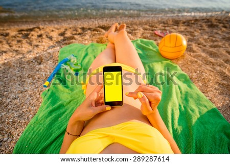 Young woman in swimsuit using mobile phone with empty screen for copy paste lying on the green towel on the beach. Top view focused on the hand with phone. - stock photo