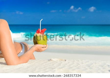 Young woman in swimsuit with coconut cocktail on the beach, seychelles.