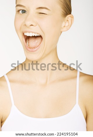 Young woman in tank top winking, portrait - stock photo