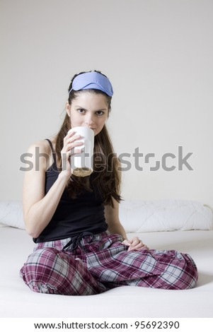 Young woman in the bed, with a cup of tea and blinkers in her head