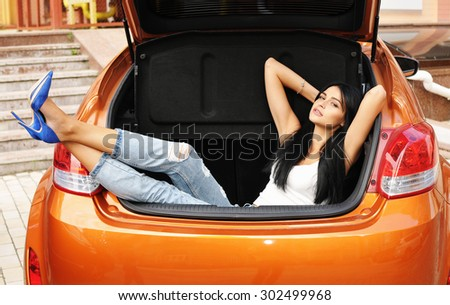 Young woman in the car trunk - stock photo
