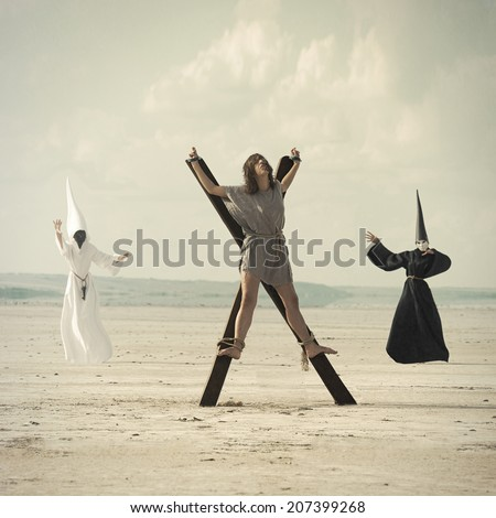 Young  woman in the desert with two mysterious persons in background - stock photo