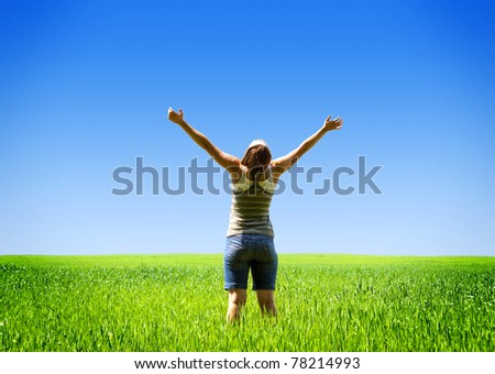 Young woman in the field happy and laughing.