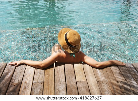 Young woman in the hat relaxing at the pool