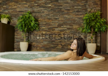 Young woman in the hot tub - stock photo