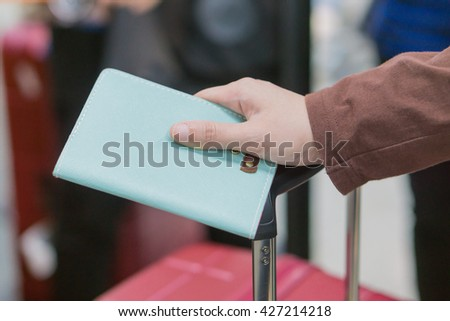 Young woman in the international airport holding passport in her hands,Tourism concept, traveler's passport.Traveling business women handing passport - airport security,selective focus,vintage color