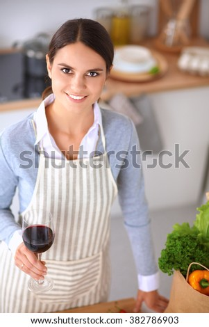 Young woman in the kitchen with glasses of a wine