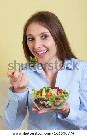 Young woman in the living room loves fresh salad
