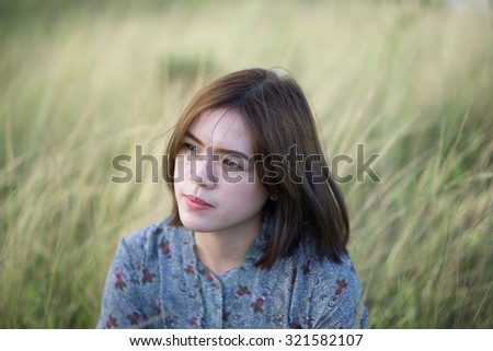 Young woman in the meadow. Pretty girl portrait in vintage style