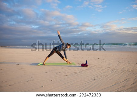 Young woman in the middle of a yoga pose on the beach at sunrise on her yoga-mat - stock photo
