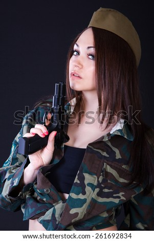 Young woman in the military uniform with the gun over black background - stock photo