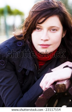 Young woman in the park staring at camera. - stock photo