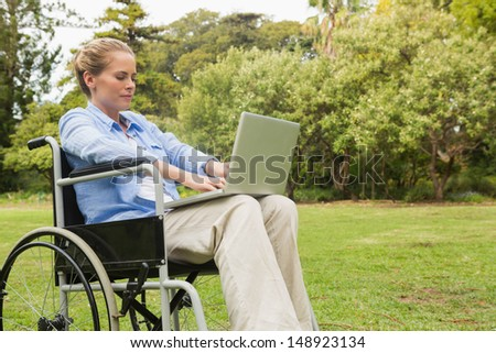Young woman in the park using a laptop in her wheelchair - stock photo