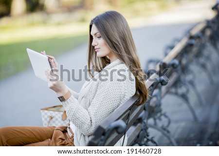 Young woman in the park with tablet - stock photo