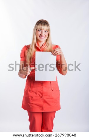 Young woman in the pink form holding holding a blank board for text