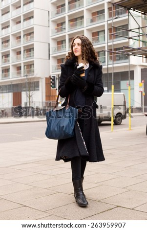 young woman in the street with a coffee