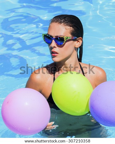 young woman in the swimming pool with sunglasses and balloons