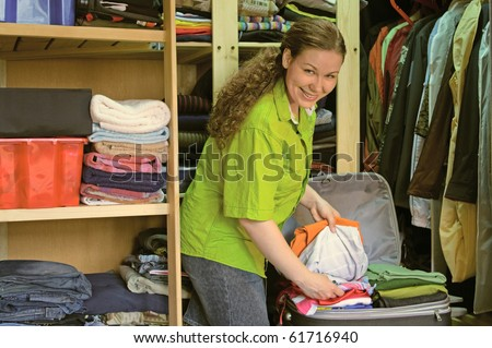 Young woman in the wardrobe packs things into a suitcase - stock photo