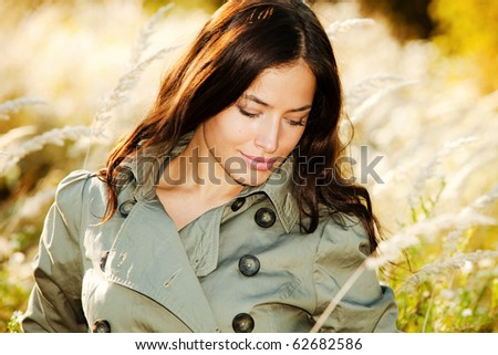 young woman in topcoat walking accros the autumn meadow, sunny autumn day - stock photo