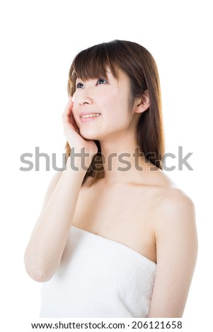 young woman in towel touching her face, isolated on white background