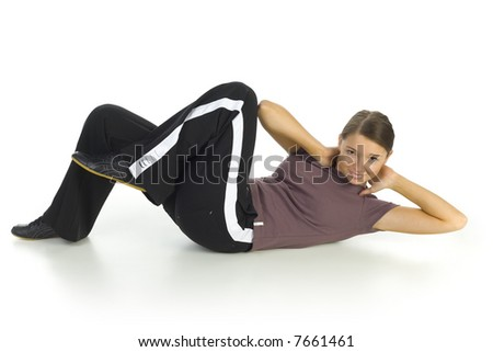 Young woman in tracksuit lying on the floor and doing some kind of exercise. Isolated on white in studio. Side view, whole body - stock photo