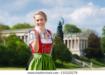 Young woman in traditional Bavarian clothes - dirndl or tracht - in front of Bavaria in Munich - stock photo