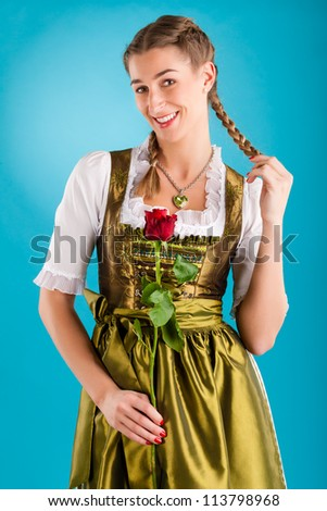 Young woman in traditional Bavarian clothes - dirndl or tracht with a rose