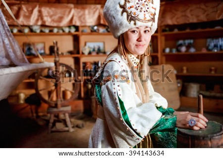 Young woman in traditional yurt dwelling. - stock photo