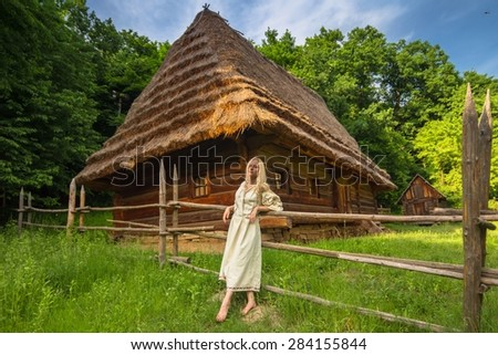 Young woman in ukrainian national costume near old wooden house (wide angle lense) - stock photo