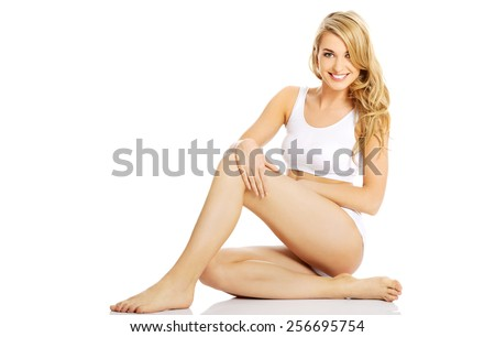 Young woman in underwear sitting on the floor - stock photo